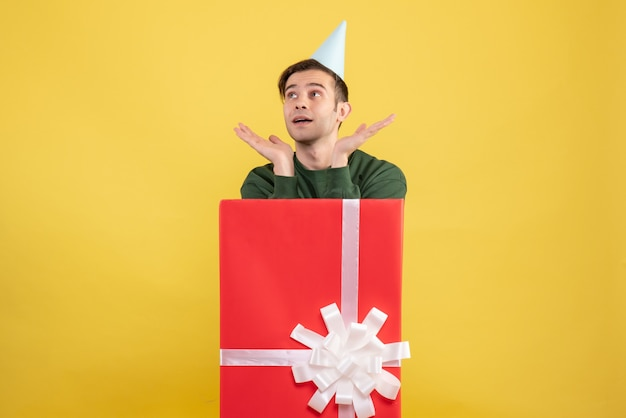 Front view young man with party cap standing behind big giftbox on yellow background