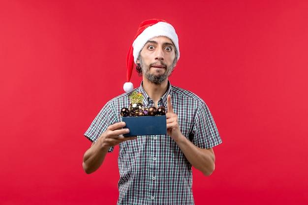 赤い背景の上のプラスチックのおもちゃと正面図の若い男