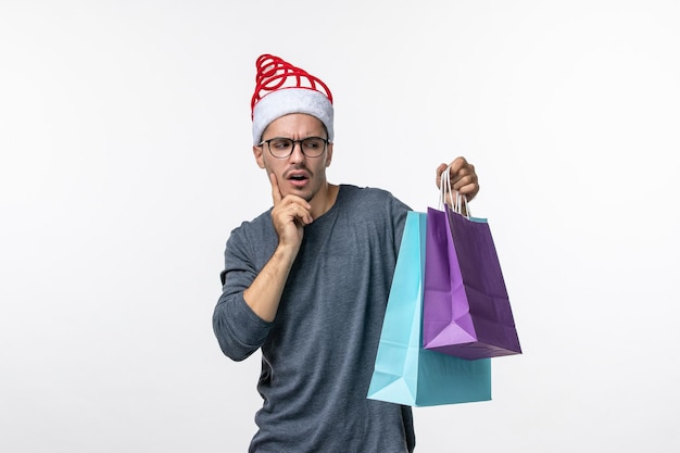 Front view of young man with presents after shopping on white wall