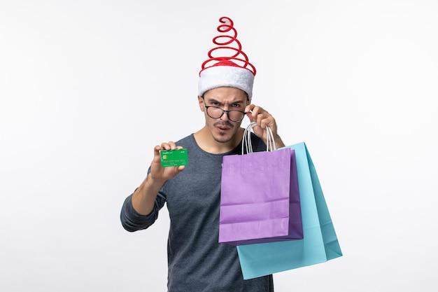 Vista frontale del giovane con regali e carta bancaria sul muro bianco