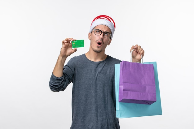 Front view of young man with presents and bank card on white wall