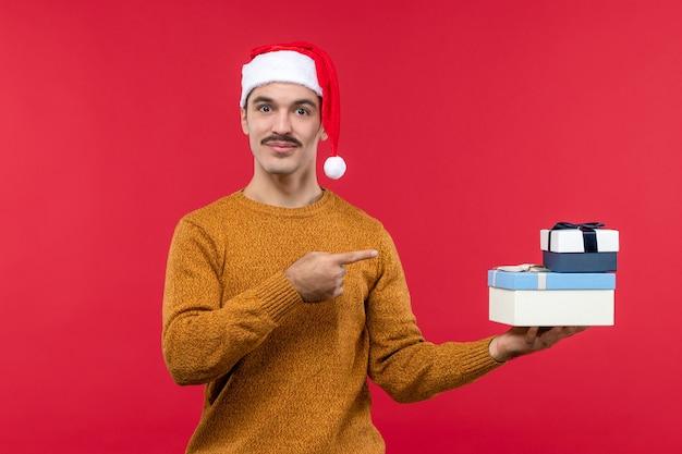 Vista frontale del giovane con regali sulla parete rossa