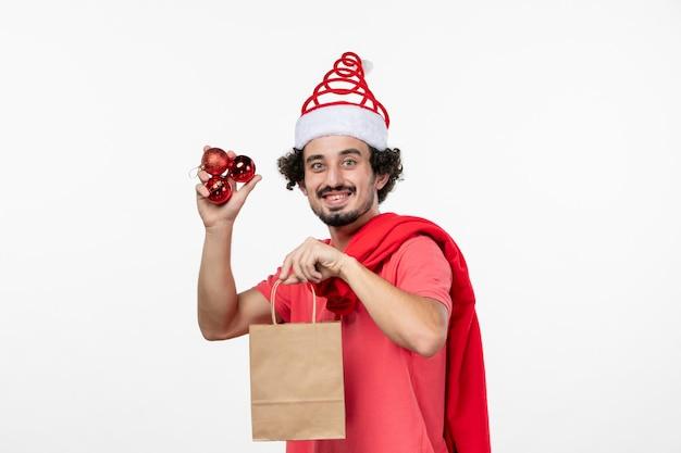 Vista frontale del giovane con regali e giocattoli sul muro bianco