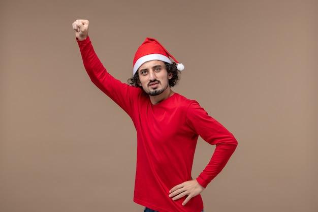 갈색 책상 크리스마스 감정 휴일에 빨간 크리스마스 케이프와 전면보기 젊은 남자