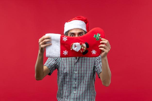 Vista frontale del giovane con il calzino rosso di natale sulla parete rossa