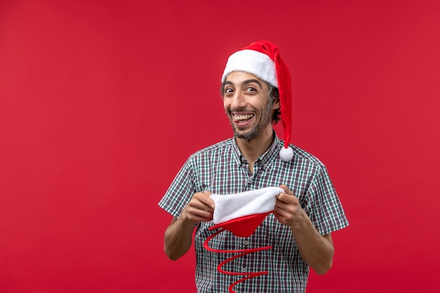 Front view of young man with red christmas toy cap on red wall