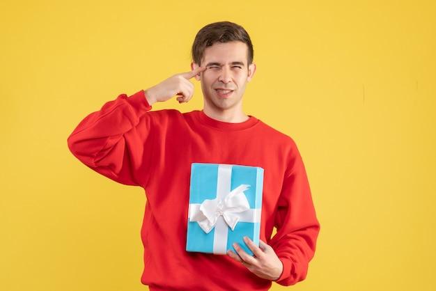 노란색 배경에 눈을 감고 빨간 스웨터와 전면보기 젊은 남자