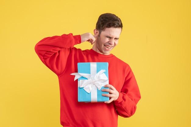 노란색 배경에 그의 눈을 감고 빨간 스웨터와 전면보기 젊은 남자