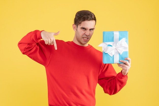 Front view young man with red sweater finger pointing down on yellow background