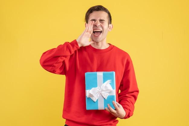 노란색 배경에 누군가를 환영하는 빨간 스웨터와 전면보기 젊은 남자