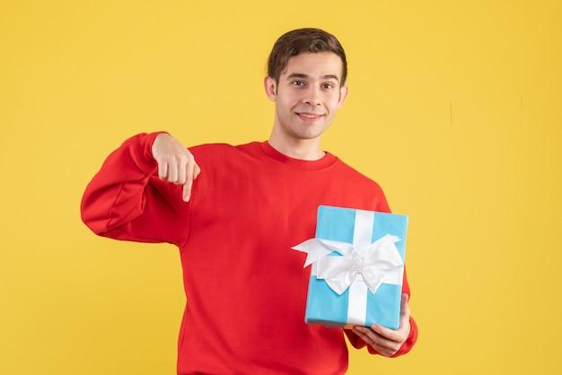 Вид спереди молодой человек с красным свитером, держащий синюю подарочную коробку на желтом фоне