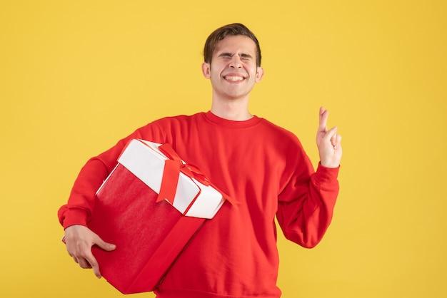 Вид спереди молодой человек в красном свитере делает знак удачи на желтом фоне