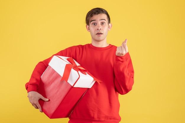 노란색 배경에 돈을 만드는 빨간 스웨터와 전면보기 젊은 남자