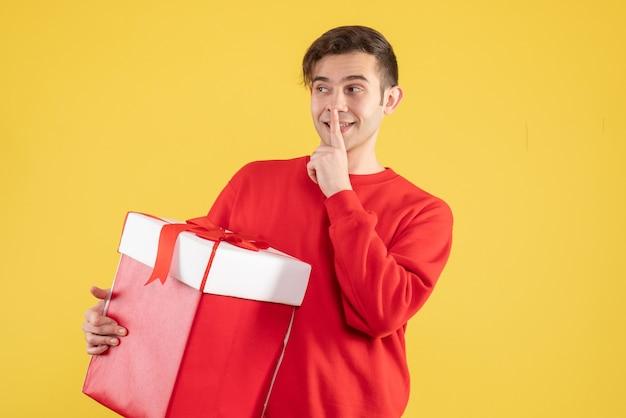 노란색 배경에 쉿 기호를 만드는 빨간 스웨터와 전면보기 젊은 남자