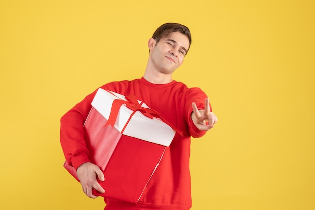 Вид спереди молодой человек в красном свитере делает знак победы на желтом фоне