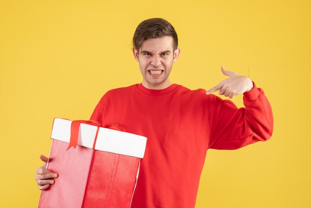 黄色の背景に自分自身を指している赤いセーターと正面図の若い男