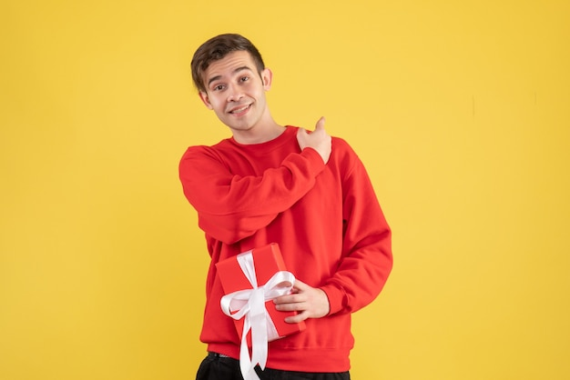 Front view young man with red sweater pointing at back on yellow background