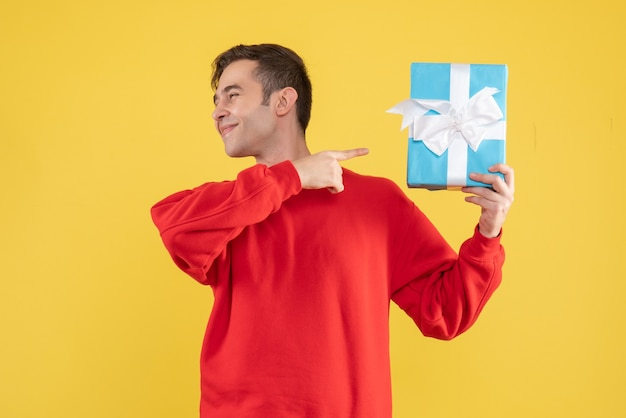Front view young man with red sweater pointing at gift box on yellow background