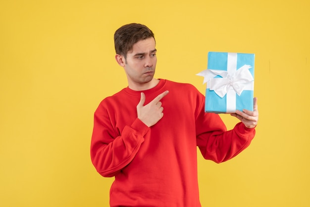 Front view young man with red sweater pointing at gift on yellow background