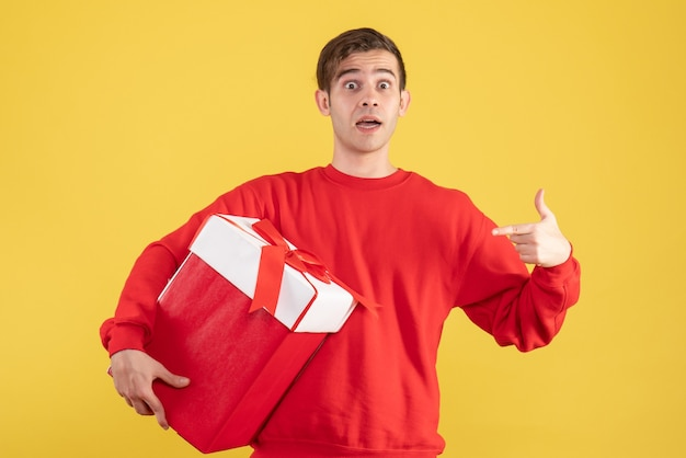 Front view young man with red sweater pointing at himself on yellow background