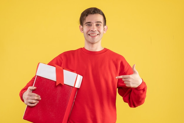 Front view young man with red sweater pointing at his gift on yellow background