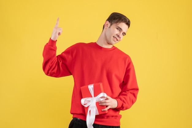 Front view young man with red sweater pointing with finger up on yellow background