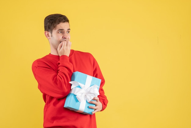 Front view young man with red sweater standing on yellow background with copy space