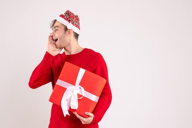 白い背景の上の誰かを歓迎するサンタの帽子をかぶった正面図の若い男空きスペースクリスマスの写真