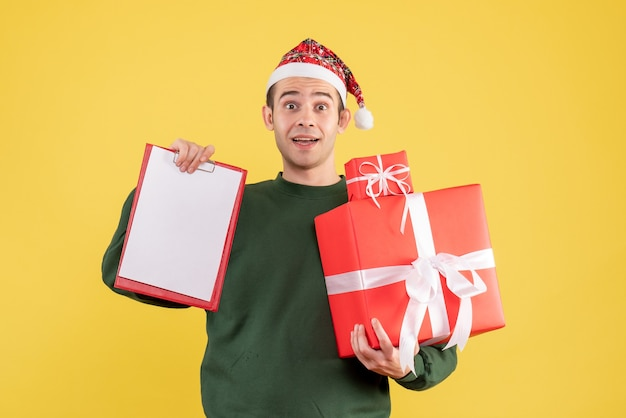 Front view young man with santa hat holding gift and clipboard standing on yellow background