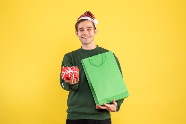 Вид спереди молодой человек в шляпе санта-клауса, держащий зеленую хозяйственную сумку и подарок, стоящий на желтом фоне копией пространства