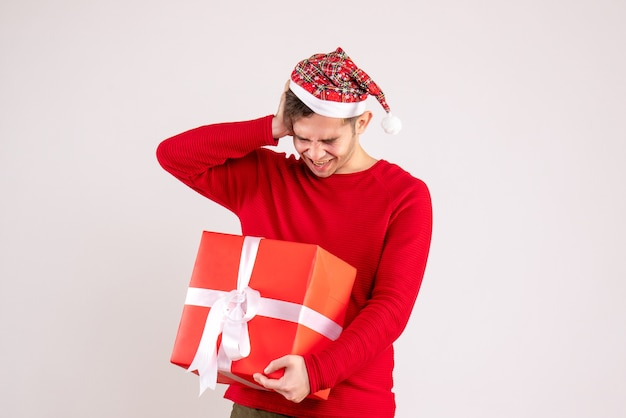 Front view young man with santa hat holding his head on white background