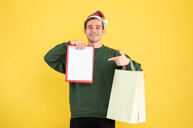 黄色の背景のコピースペースに立っている買い物袋とクリップボードを保持しているサンタ帽子を持つ正面図の若い男