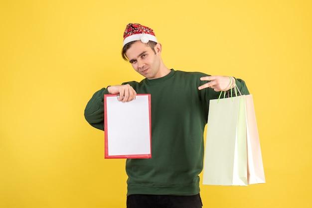 黄色の背景の上に立っている買い物袋とクリップボードを保持しているサンタ帽子を持つ正面図の若い男