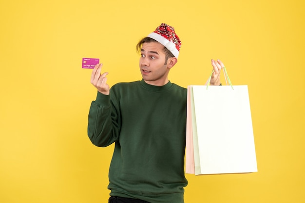 Front view young man with santa hat holding shopping bags and card standing on yellow background copy place