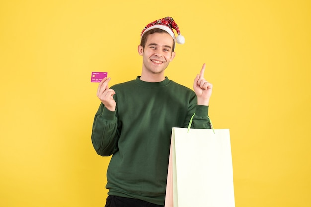 Front view young man with santa hat holding shopping bags and card standing on yellow background copy space