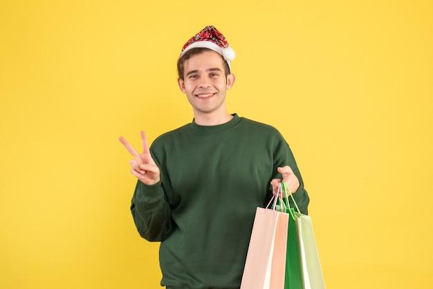 黄色の背景に勝利のサインを作る買い物袋を保持しているサンタの帽子をかぶった正面図