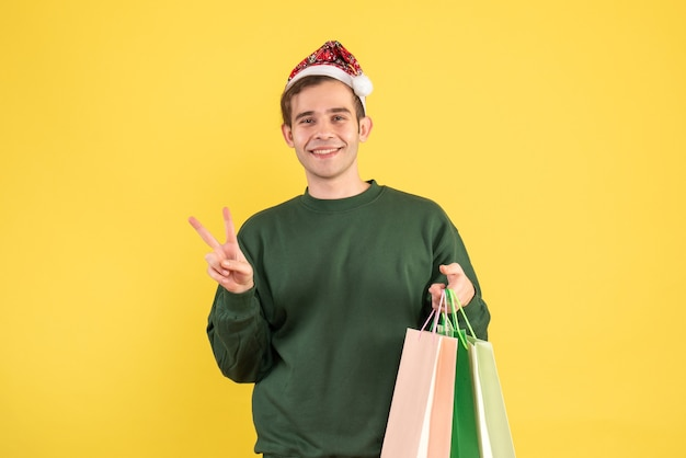 Front view young man with santa hat holding shopping bags making victory sign on yellow background