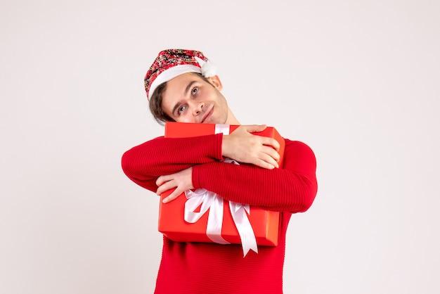 白い背景の上の彼の贈り物をしっかりと保持しているサンタ帽子を持つ正面図の若い男