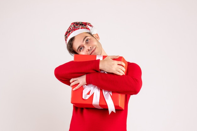 Front view young man with santa hat holding tightly his gift on white background