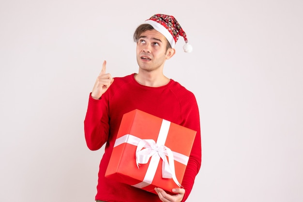 Front view young man with santa hat looking at high standing on white background