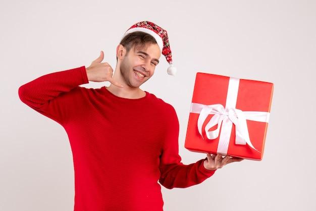 サンタの帽子をかぶった正面図の若い男は、白い背景の上の電話ジェスチャーを呼び出します