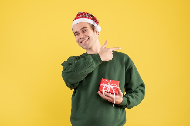 Front view young man with santa hat pointing at something on yellow background