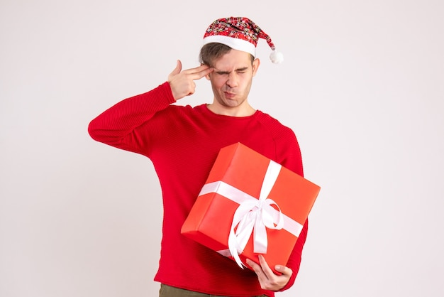Front view young man with santa hat putting finger gun to his temple standing on white background