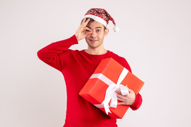 Front view young man with santa hat putting okey sign in front of an eye on white background