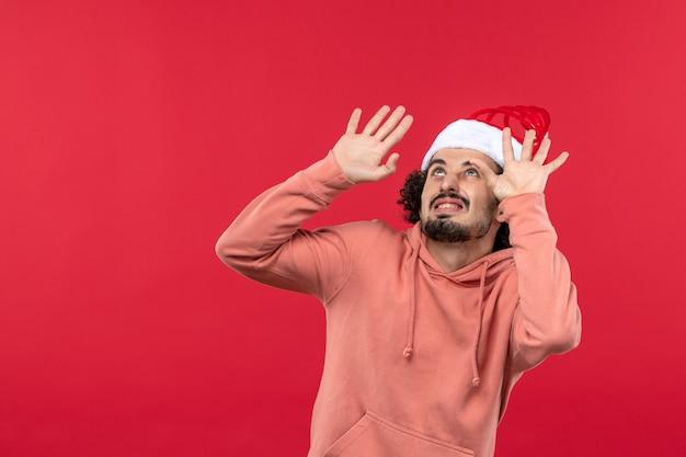 Vista frontale del giovane con espressione spaventata sul muro rosso