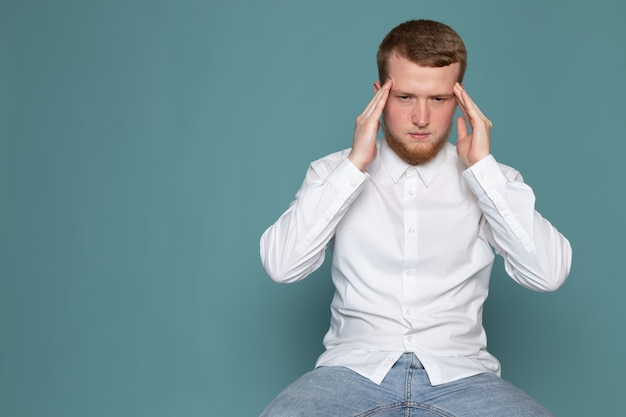 A front view young man with severe headache in white t-shirt on the blue space