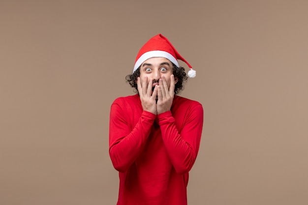 Front view young man with shocked expression on brown background christmas emotion holiday