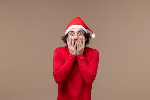 Вид спереди молодой человек с шокированным выражением лица на коричневом фоне рождественских эмоций