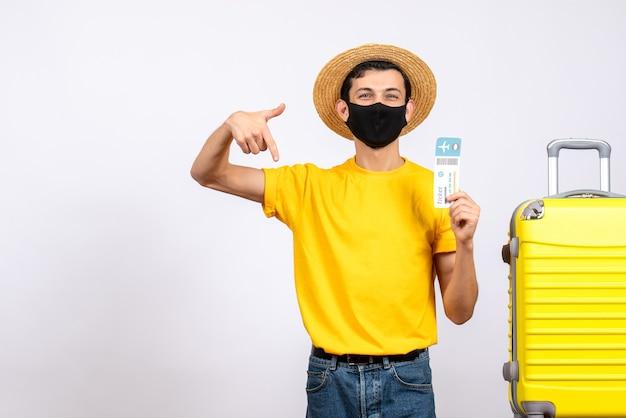 旅行チケットを保持している黄色のスーツケースの近くに立っている麦わら帽子とマスクを持つ正面図の若い男