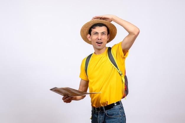 Вид спереди молодой человек в соломенной шляпе и желтой футболке держит карту